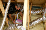 Picture of a man working on duct work in an attic.